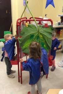 Preschoolers painting leaves to make prints.